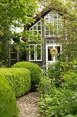 Natursteinweg mit Buchsbaumhecke führt zu Wohnhaus