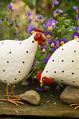 Hen figurines in front of violas