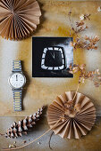 Black-and-white photo in hand-made frame, dried flowers, wristwatch, pine cone and paper rosettes