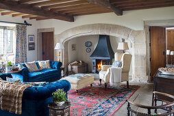 Log burner in inglenook fireplace and blue sofa set in living room of old building