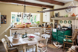Dining table and green wood-fired stove in rustic kitchen