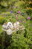 Vintage garden decorations in herbaceous border