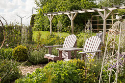 Wooden chairs in seating area in front of pergola in garden