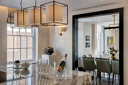 Champagne on kitchen island with marble worksurface and view into dining room