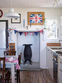 Country house kitchen with iron stove in disused fireplace, above it DIY pennant chain and England flag in picture frame
