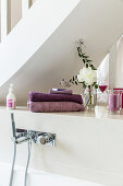 Towels, flowers and scented candle on shelf above wall-mounted bath taps
