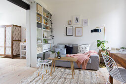 Grey sofa next to tall shelves in living room with wide open doorway