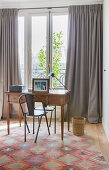Metal chair at antique desk on colourful rug in front of window