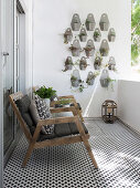 Wooden armchairs with cushions, black and white floor tiles and foliage plants in wall-mounted pots on balcony
