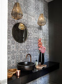 Sink on black washstand in guest toilet with patterned wall tiles