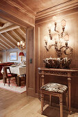 Opulent wall lamps above Baroque console table outside dining room