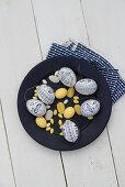 Blau-weiß bemalte Ostereier, gelbe Zuckereier und Marzipaneier auf Teller
