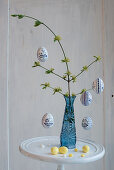 Easter eggs hung from branch in blue glass vase