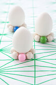 White eggs stood on circlets of wooden beads