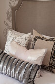 Collection of scatter cushions on double bed with tall headboard