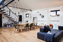 Grey sofa bed, dining area and gymnastic rings in open-plan interior