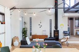 Grey sofa bed and log burner in open-plan interior