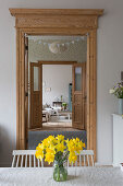 Vase of daffodils on table and view into living room through open doors