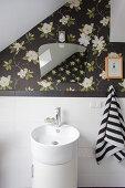 Vintage-style mirror on dark floral wallpaper above sink