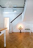 Stuhl und Kerzenleuchter in Halle mit Fischgrätparkett, Treppenaufgang und weißen Wänden