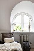 Bett mit Kissen und Lammfell vor Rundbogenfenster