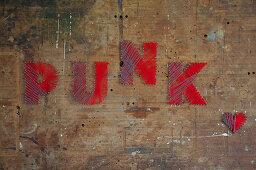 'Punk' written in red lettering on old wooden door