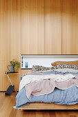 Double bed against wall with wooden paneling and alcove