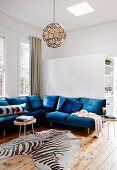 Blue seating and zebra fur in a bright living room with wooden floorboards