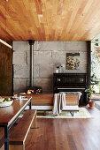 Essbereich in offenem Wohnraum mit Betonwand und Holzdecke, im Hintergrund Schwedenofen und Klavier