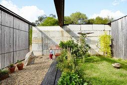 Eingefasster Garten mit Rasenfläche, Kleinkind im Hintergrund