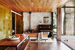 Dining area in an open living room with concrete wall and wooden ceiling, in the background Swedish stove and piano
