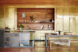 Kitchen and dining area in an open living room with patinated brass cladding