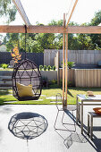 Hammock chair on sunny terrace with pergola in modern garden