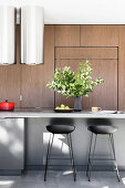 Bar stool on the island in a modern kitchen with wooden fronts