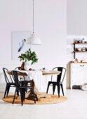 Schwarze Metallstühle um runden Holztisch mit Balusterfuß