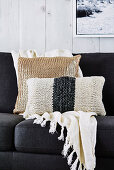 Knitted pillows and plaid with tassels on the sofa