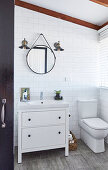 Vanity unit next to toilet in bathroom with white wall tiles