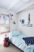 Trommeln als Nachttisch neben Bett im Jungenzimmer mit weiß gestrichener Holzverkleidung