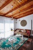 Braune Ledercouch und weiße Tische im Wohnzimmer mit Holzbalkendecke
