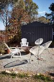 weiße Stühle um Feuerschale auf Terrassenplatz in herbstlichem Garten