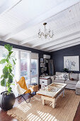 Gray upholstered furniture, vintage coffee table and classic leather chair with fur blanket next to houseplant in living room
