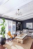 Graue Polstergarnitur, Vintage Couchtisch und Klassiker Lederstuhl mit Felldecke neben Zimmerpflanze im Wohnzimmer