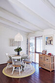 Round table with wooden chairs on carpet in dining area with white wood paneling