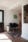 Two black designer chairs and ethnic rug in foyer