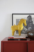 Yellow horse sculpture on stack of books on top of red cabinet
