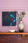 Ornamental cabbage and lucky bamboo in vase against pink wall