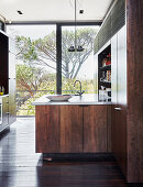 Moderne Küche mit dunklen Holzfronten und Glasfront
