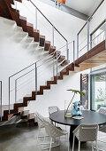 Runder Esstisch mit Polsterstühlen unter den freitragenden Treppen