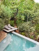 Zwei Liegen auf dem Platau am Infinity-Pool im naturnahen Garten