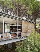 Modernes Architektenhaus auf Stelzen mit offener Fassade im Wald